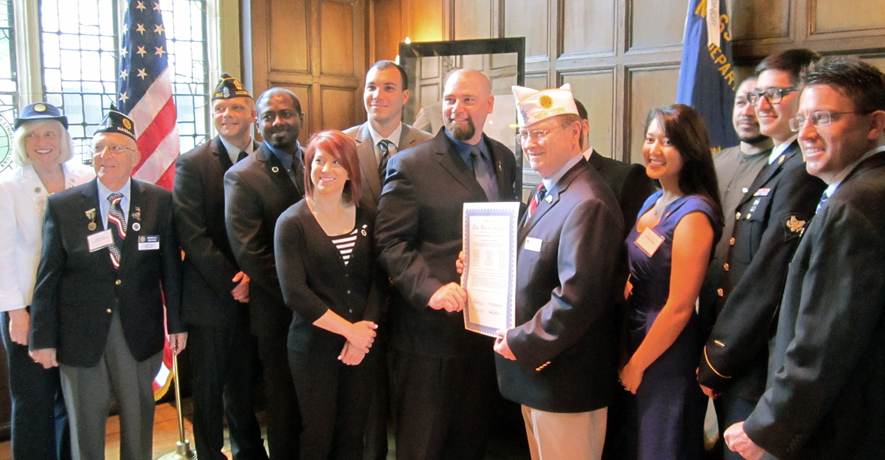Legionnaires, student veterans, Conolly family members gather around as Department Commander Ken Governor presents the charter to Conolly Post 2014 Commander Michael Knauer. Photo by James Randle.