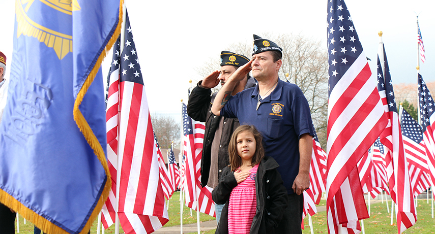 Legionnaires Brian Lazore, left, and Jim George render salutes during Veterans Day ceremonies along the flag-strewn Memorial Parkway in Utica. With them is Lazore's daughter, Olivia.