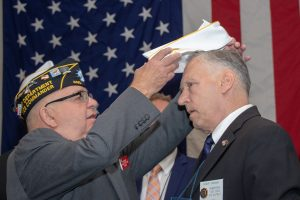Legionnaire of the Year program Chair Mike McDermott places the Department white hat on Robert Gardner.